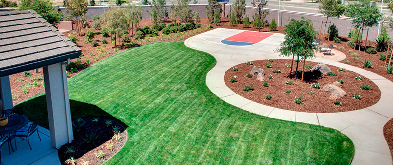 an arial photo of a backyard with very nice landscaping and a circular walkway