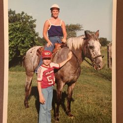 an image of Darryl next to a horse with a young girl atop the horse riding it