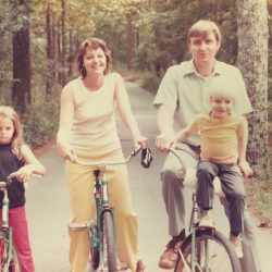 an image of Darryl as a young boy outdoors on bicycles with his family