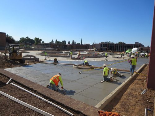 an image of workers pouring and smoothing out the concrete as it dries