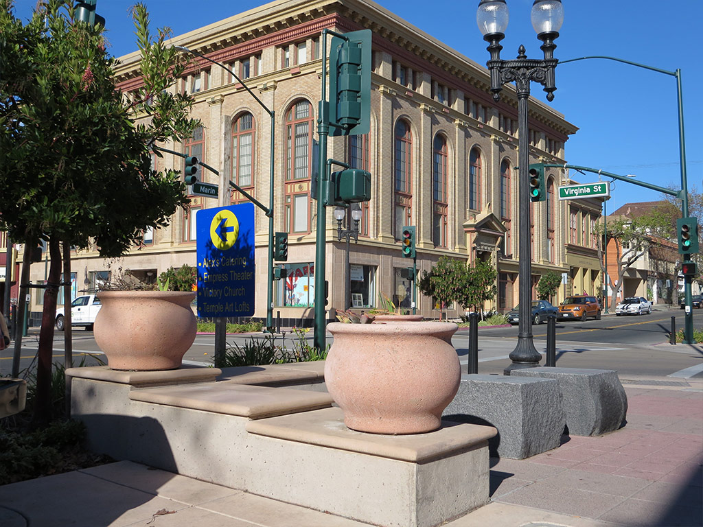 an image of a lovely street corner adorned with lots of concrete pots and custom pavers inlaid in the ground