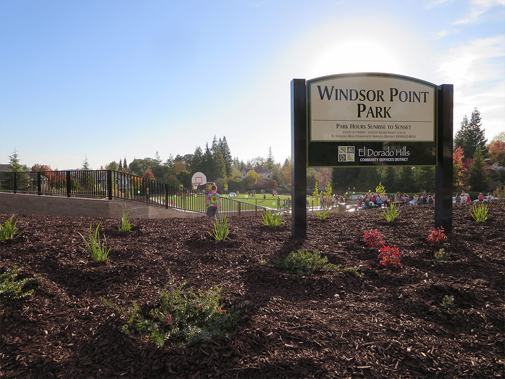 a sign of Windsor Point Park with the park structures in the background and the sun setting behind the sign